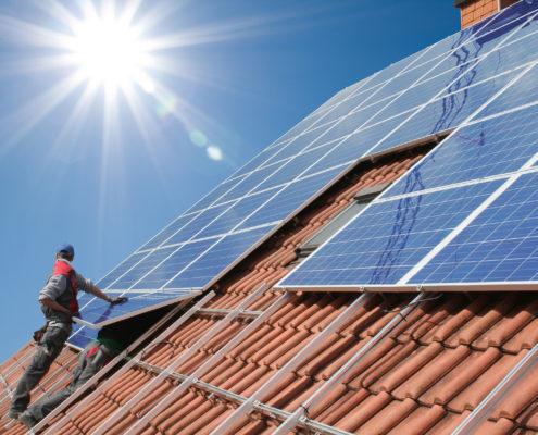 Arbeiter montieren Photovotaik-Module auf einem Hausdach; strahlende Sonne.